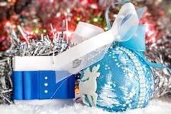 Weihnachtsgeschenk und Weihnachtsball auf Schnee gegen einen Hintergrund des glänzenden Lamettas Glühende Leuchten Bokeh Lizenzfreie Stockfotografie