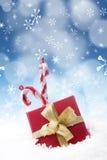 Weihnachtsgeschenk und Zuckerstange unter Schnee Lizenzfreie Stockbilder