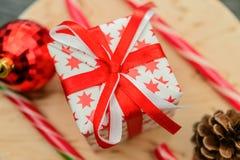 Weihnachtsgeschenk, verziert mit den roten Sternen, gebunden mit einem roten Band Stockbilder