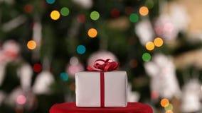 Weihnachtsgeschenk vor verziertem Weihnachtsbaum stock video footage