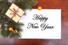 Weihnachtsgeschenkbox auf einem hölzernen Desktop mit Buchstaben für Kopienraum Lizenzfreie Stockfotos