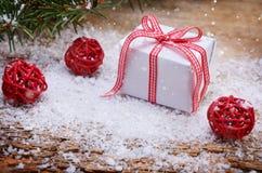 Weihnachtsgeschenkbox auf schneebedecktem hölzernem Hintergrund Lizenzfreie Stockfotos