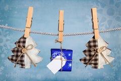 Weihnachtsgeschenkbox, die an der Wäscheleine hängt Stockbild