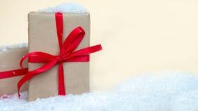 Weihnachtsgeschenkbox eingewickelt im Kraftpapier mit rotem Band stockbilder
