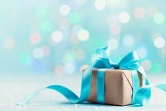Weihnachtsgeschenkbox gegen blauen bokeh Hintergrund Explosion von Farben und von Formen stockbild