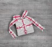 Weihnachtsgeschenkbox mit Band auf grauem hölzernem Hintergrund Lizenzfreie Stockfotografie