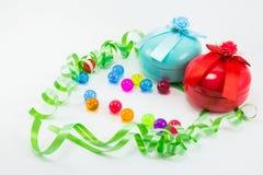 Weihnachtsgeschenkbox mit Band- und Farbplastikbällen Lizenzfreie Stockfotos