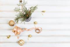 Weihnachtsgeschenkbox mit Bandbogen und Ball spielen auf weißem hölzernem Hintergrund Lizenzfreie Stockfotografie