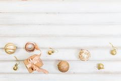 Weihnachtsgeschenkbox mit Bandbogen und Ball spielen auf weißem hölzernem Hintergrund stockfoto
