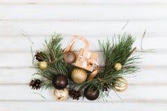 Weihnachtsgeschenkbox mit Bandbogen und NiederlassungsWeihnachtsbaum und Ballspielzeug und Kegel auf weißem hölzernem Lizenzfreie Stockfotografie