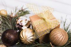 Weihnachtsgeschenkbox mit Bandbogen und NiederlassungsWeihnachtsbaum und Ballspielzeug und Kegel auf weißem hölzernem Stockbilder