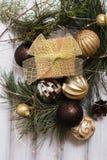 Weihnachtsgeschenkbox mit Bandbogen und NiederlassungsWeihnachtsbaum und Ballspielzeug und Kegel auf weißem hölzernem Stockfoto