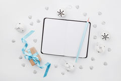 Weihnachtsgeschenkbox mit blauem Band, leerem Notizbuch und Klingelglocke auf weißem Schreibtisch oben Explosion von Farben und v Stockbilder