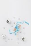 Weihnachtsgeschenkbox mit blauem Band und Klingelglocke auf weißem Hintergrund von oben Explosion von Farben und von Formen Model Lizenzfreie Stockfotos