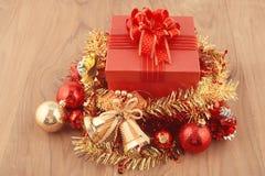 Weihnachtsgeschenkbox mit Dekorationen und Farbball auf Holz Lizenzfreie Stockbilder