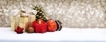 Weihnachtsgeschenkbox mit der Dekoration lokalisiert auf goldenem Hintergrund Lizenzfreie Stockfotografie