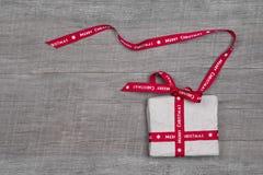 Weihnachtsgeschenkbox mit rotem Band auf grauem hölzernem backgrou Stockbilder