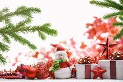 Weihnachtsgeschenkbox, -Schneemann, -flitter und -Tannenzweige auf weißem Hintergrund Stockbild