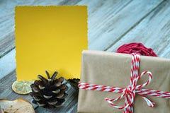 Weihnachtsgeschenkbox und gelbe Grußkarte Stockfotografie