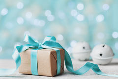 Weihnachtsgeschenkbox- und -klingelglocke gegen Türkis bokeh Hintergrund Explosion von Farben und von Formen Lizenzfreies Stockfoto