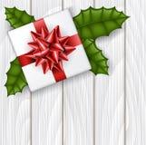 Weihnachtsgeschenkbox von der Draufsicht mit rotem Band und grüne Stechpalme treiben Blätter Stockfotografie
