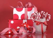 Weihnachtsgeschenkboxen auf rotem Hintergrund, mit StreifenZuckerstangen Stockfotos