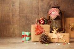 Weihnachtsgeschenkboxen und rustikale Verzierungen auf Holztisch stockfoto