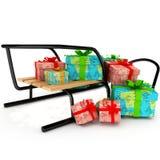 Weihnachtsgeschenke auf einem hölzernen Schlitten über Weiß Lizenzfreie Stockbilder