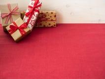 Weihnachtsgeschenke auf roter Tischdecke Stockbild