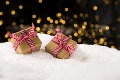 Weihnachtsgeschenke auf Schnee, Weihnachtslichthintergrund Lizenzfreies Stockfoto