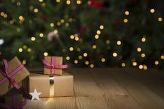 Weihnachtsgeschenke auf Tabelle, Lichthintergrund Stockfotos
