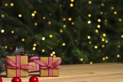 Weihnachtsgeschenke auf Tabelle, Weihnachtsbaumhintergrund Stockbilder