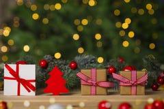 Weihnachtsgeschenke auf Tabelle, Weihnachtsbaumhintergrund Lizenzfreie Stockbilder