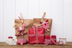 Weihnachtsgeschenke eingewickelt in den Papiertüten mit dem roten Weiß überprüft Stockfoto