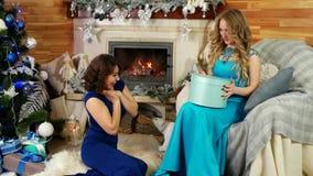 Weihnachtsgeschenke, frohe schöne Frau geben ein Geschenk, Freundaustauschüberraschungen, neues Jahr ` s Eve, Mädchen sitzen durc stock video footage
