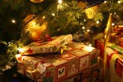 Weihnachtsgeschenke geholt von Santa Claus, die unter dem beleuchteten Weihnachtsbaum liegt lizenzfreie stockfotos