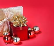 Weihnachtsgeschenke. Geschenkboxen mit Goldbogen und glänzenden Bällen Lizenzfreie Stockbilder
