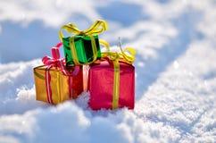 Weihnachtsgeschenke im Schnee Stockbild