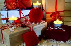Weihnachtsgeschenke, -kerzen und -Kleinigkeiten auf hölzernem Hintergrund Lizenzfreie Stockfotos