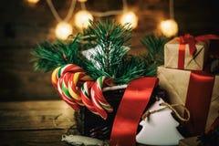 Weihnachtsgeschenke mit den Kästen, Koniferen, Korb, Zuckerstange Kegel auf hölzernem Hintergrund Abbildung der roten Lilie Lizenzfreies Stockbild