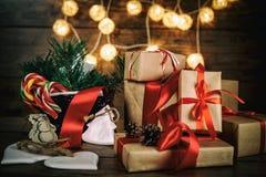 Weihnachtsgeschenke mit den Kästen, Koniferen, Korb, Zuckerstange Kegel auf hölzernem Hintergrund Abbildung der roten Lilie Lizenzfreie Stockbilder