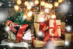 Weihnachtsgeschenke mit den Kästen, Koniferen, Korb, Zuckerstange Kegel auf hölzernem Hintergrund Weinleseart mit gezogenen Schne Stockfotografie
