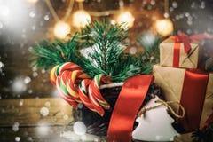 Weihnachtsgeschenke mit den Kästen, Koniferen, Korb, Zuckerstange Kegel auf hölzernem Hintergrund Weinleseart mit gezogenen Schne Lizenzfreies Stockfoto