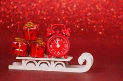 Weihnachtsgeschenke mit einer Uhr und einem Pferdeschlitten auf rotem Hintergrund, Kopienraum Stockbilder