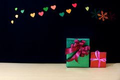 Weihnachtsgeschenke mit Herz und Schnee bokeh auf Holztisch stockbilder