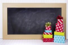 Weihnachtsgeschenke mit Kreidebrett Stockbild