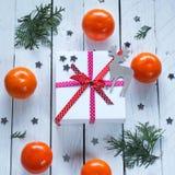 Weihnachtsgeschenke mit rotem Band und Tangerinen Lizenzfreie Stockfotos