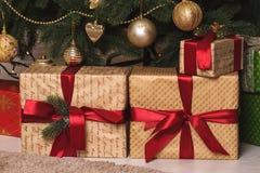 Weihnachtsgeschenke mit roten Bändern unter dem Baum Lizenzfreies Stockfoto
