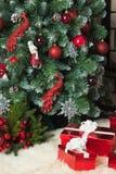 Weihnachtsgeschenke nähern sich grünem Baum mit Bällen und Spielwaren Stockfotografie
