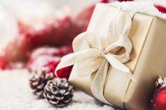 Weihnachtsgeschenke oder Geschenke mit eleganten Bogen- und Weihnachtsdekorationen auf hellem schneebedecktem Hintergrund Stockfotografie